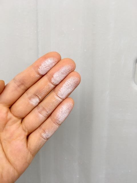 ショーキング現現象が起きている壁を触って、真っ白になっている手のひらの写真